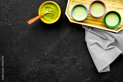 Japanise tea ceremony with matcha tea. Bowl with powder and cups with beverage on tablecloth black background top view copy space
