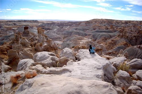 Poster Cappuccino Woman in desert badlands landscape with blue sky in New mexico badlands desert. Bisti De Na Zin.