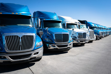 Fleet of blue 18 wheeler semi trucks