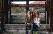 A young family of three sitting on an old concrete wal surround by old rustic wood for a family portrait