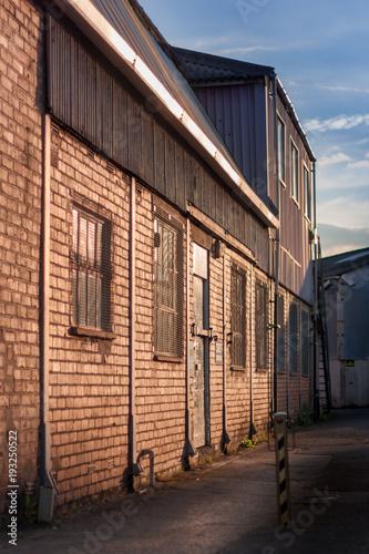 Staande foto Oude verlaten gebouwen Sunset factory brick building