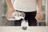 Young woman poring water from bottle to glass