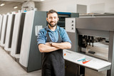 Portrait of a handsome typographer standing at the printing manufacturing with offset machine on the backgorund