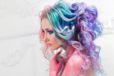 Beautiful woman with bright hair. Bright hair color, hairstyle with curls.