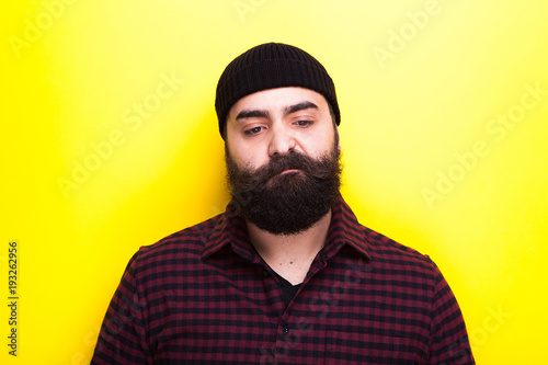 Bearded hipster wearing a hat on yellow background in studio photo