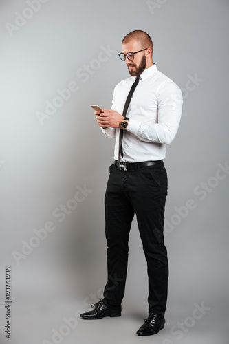 Full-length image of young unshaved man in glasses and tie chatting or working on mobile phone, isolated over gray background