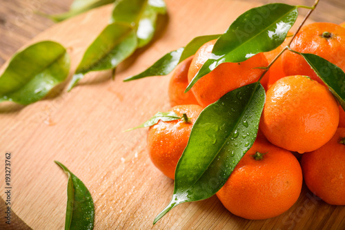 Tangerines with leaves on a wooden background.Beautiful composition of tropical fruits Mandarin on wooden background