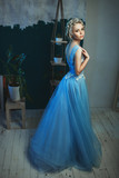 Beautiful model wearing light blue dress is posing in a studio