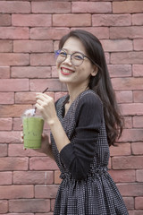 younger asian woman and glasses of ice green tea beverage in hand