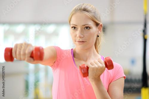 Aluminium Fitness Frau in Fitnessstudio trainiert mit Hanteln und Gewichten