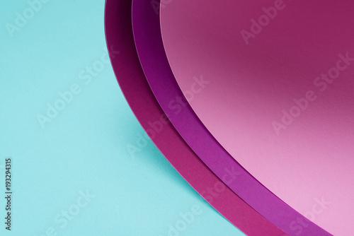 skręcony różowy i bordowy papier na turkusie