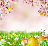Idyllic spring meadow with Easter eggs and butterflies with blossoms.