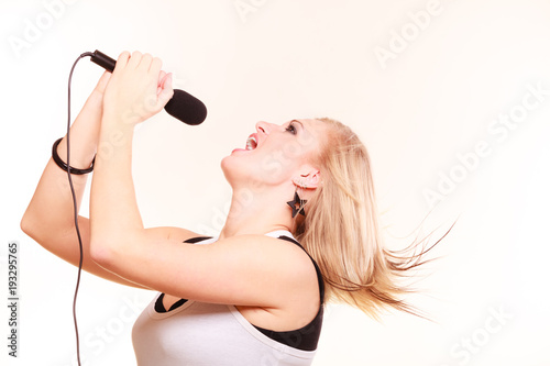 Fototapeta Blonde woman singing to microphone, profile view