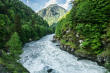 The mountain river flows between the woods of rocks. Mountain landscape.. - 193310143