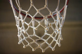 Basketball hoop with white net. Blurred background, close up view with details.