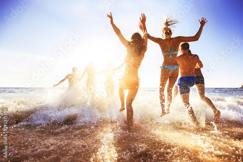 Happy friends at sunset sea beach
