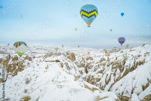 Deurstickers Lichtblauw Hot air balloons flying at snowly weather, Goreme, Cappadocia, Turkey.