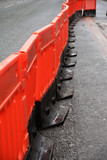 Photo of a line of plastic orange safety barriers