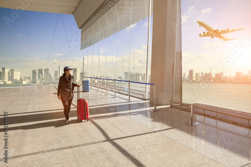 traveling-woman-with-belonging-luggage-walking-in-airport-terminal-building-and-passenger-plane-flying-over-building-in-city