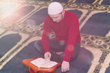 Muslim man reciting from holy book Koran, Qoran, islamic religious book