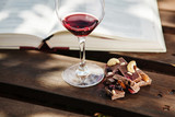 Glass with wine and pieces of chocolate near open book - 193368944