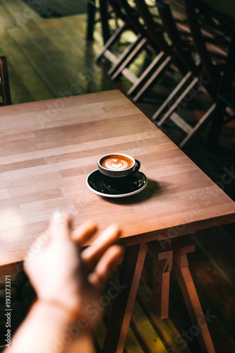Aluminium Kuala Lumpur Woman's hand reaching cappuccino coffee on a black plate from above. Light wooden table at the hipster coffee shop. Vintage color filter effect. Minimalist concept. Copyspace