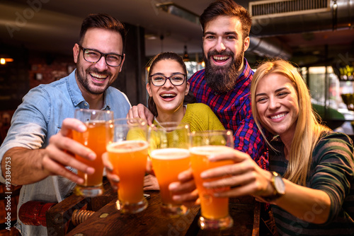 Fototapeta Group of young friends in bar drinking beer toasting