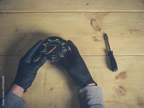 Gloved hands holding speedometer