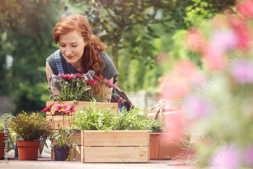 Girl smelling red flowers
