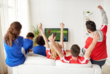 football fans watching soccer game on tv at home - 193402363