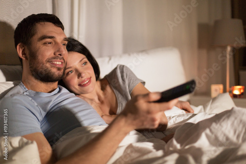 happy couple watching tv in bed at night at home