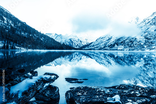 Fotobehang Nachtblauw Beautiful blue lake in the mountains. Flat mirror surface of the water under the clouds. The beauty of winter nature. A tourist Trip through the nature reserve of Altai.