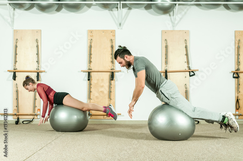 Aluminium Fitness Young beautiful fitness couple workout extreme acrobatic exercise on the ball as preparation for the competition, selective focus