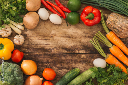 Various fresh vegetables on a wooden table. Top view.