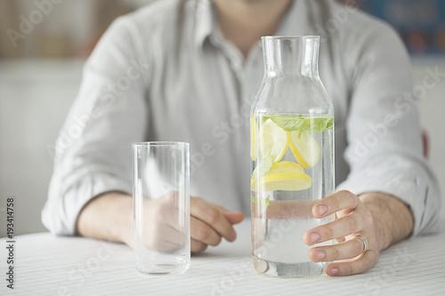 Młody człowiek ma butelkę woda i szkło w kuchni