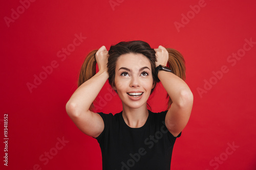 Fotobehang Kapsalon Photo of funny adult girl 20s in black t-shirt playing around and making two ponytails hairstyle, isolated over red background
