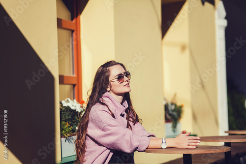 Fashion portrait pretty woman in casual style sitting in cafe