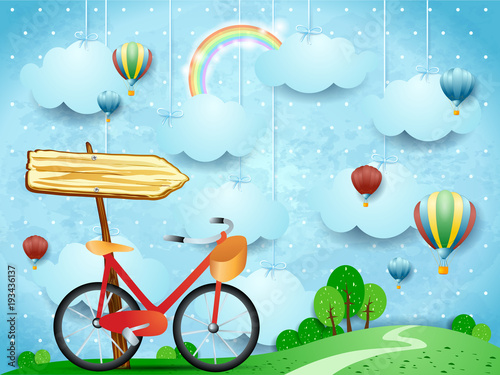 Surreal landscape with hanging clouds, arrow sign and bike