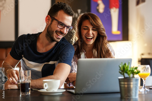 Fototapeta Young couple sitting at the internet cafe and relaxing on coffee break.Using laptop and free wireless.