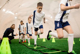 Row of boys running on green football field during training with instructor - 193439747