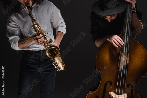 duet of jazzmen playign cello and sax on black