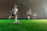Three boys in uniform running after ball down green field while training indoors