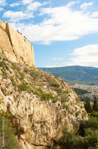Tuinposter Athene Bottom view on the wall of the Acropolis and tourists on it against the blue sky, Athens, Greece.