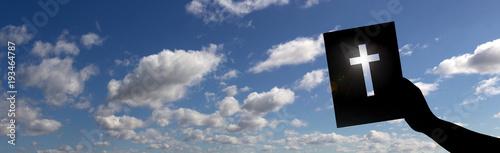 Hand hält Bibel mit Kreuz vor blauem Himmelspanorama