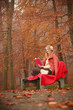 Blonde girl reading book in autumn scenery