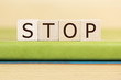 stop written in wooden cubes on a green book