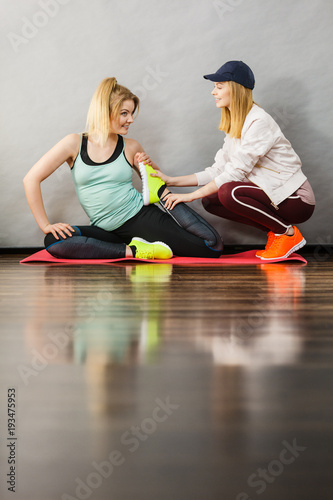 Sticker Woman in sportswear stretching legs with trainer
