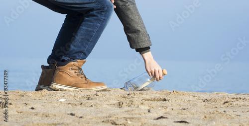 Kind hebt eine Flaschenpost am Strand auf