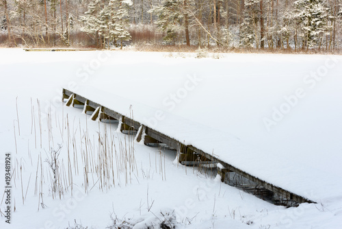 Small and narrow wooden pier in wintry forest fishing lake, Snow and ice on lake and surrounding landscape.