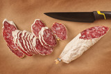 Salami slices with black knife on paper background - 193483914